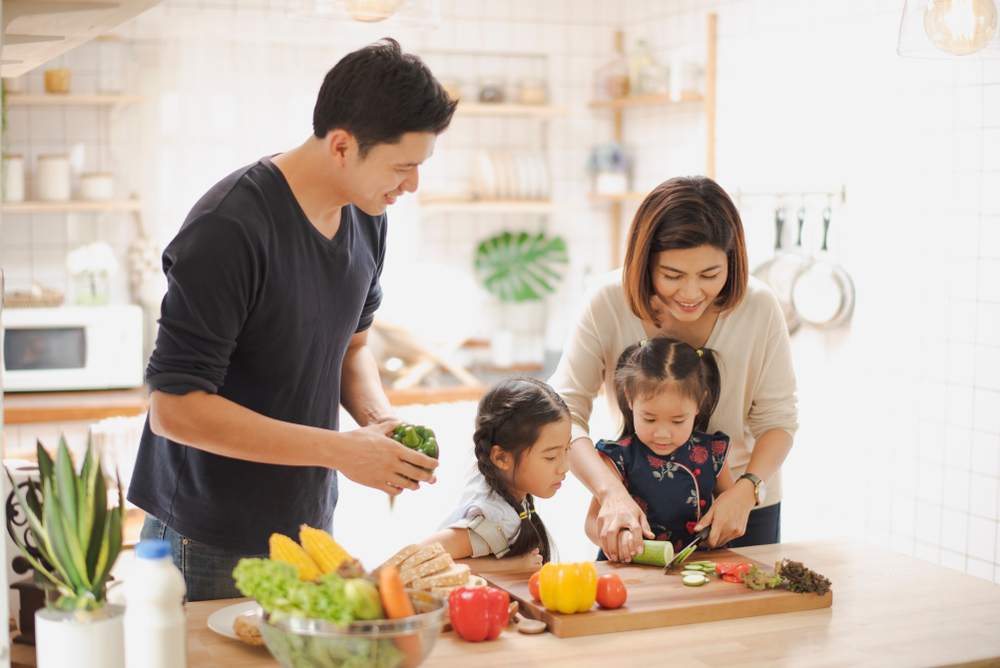 family teaching their kids to prepare healthy foods